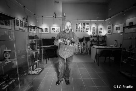Marek Mazur nel negozio ci mostra una macchina fotografica scolpita nel legno.