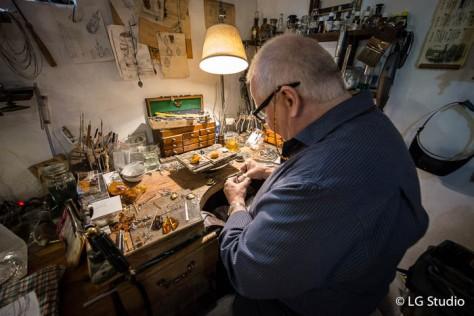 Boguslaw Kolpak, al suo banco da lavoro, ci mostra la lavorazione dell'ambra.